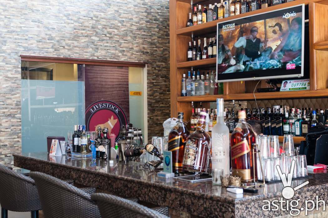 The bar has a television set surrounded by bottles of alcohol