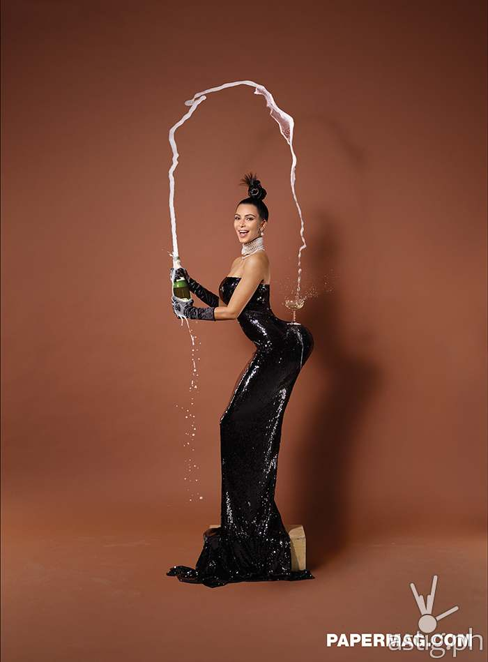 Kim Kardashian balances a champagne glass on her butt while wearing MIKIMOTO necklaces and earrings, customized dress and vintage gloves
